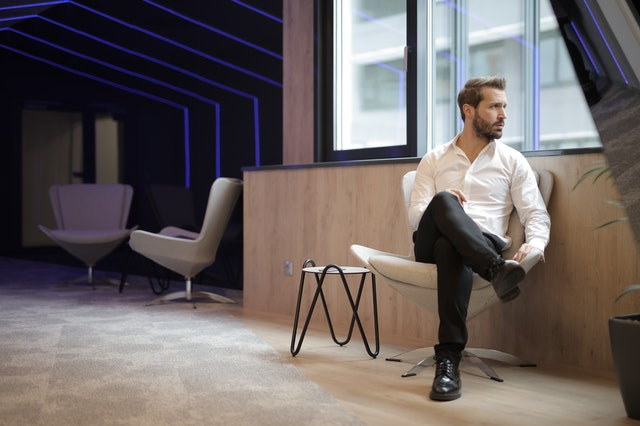 confident-businessman-sitting-on-armchair-near-window-in-3966779
